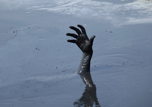 hand of a man drowning in mud