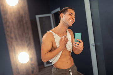 Joyful nice man taking photo of his body