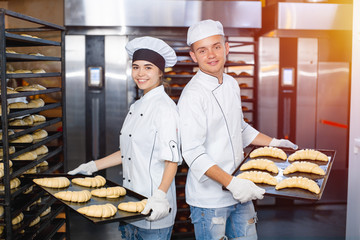 baker boy and girl with baking sheets with raw dough on the background of an industrial oven in a bakery.