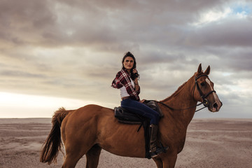 Woman horse riding on beach in evening