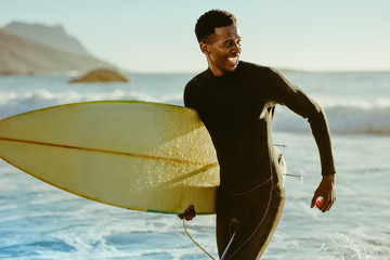 Smiling african male surfer Wall mural