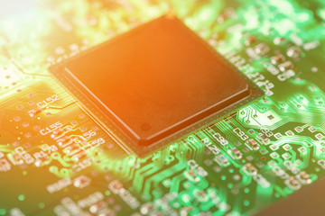 Backlit green printed circuit board with the processor is burning orange, background texture
