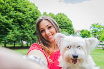 Pretty young woman doing selfie with her dog at the park