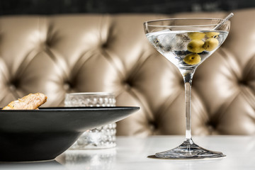 Beautiful glass of martini with olives accompanied by a gourmet dish.