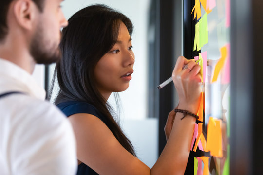 Focused asian businesswoman writing on sticky notes on glass