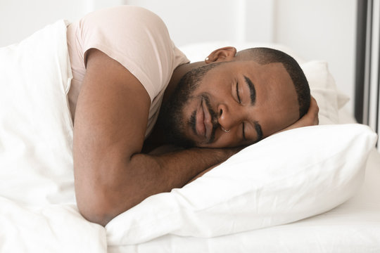 Serene calm young black man sleeping well alone in bed