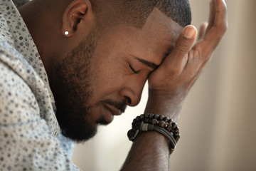 Upset stressed young african american man coping with strong headache