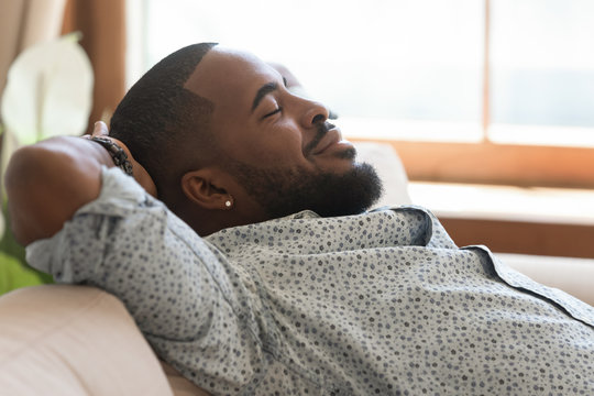 Calm lazy african american young man relaxing leaning on sofa