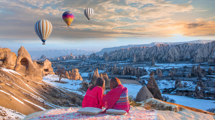 Photo sur Aluminium Montgolfière / Dirigeable Hot air balloon flying over spectacular Cappadocia - Girls watching hot air balloon at the hill of Cappadocia