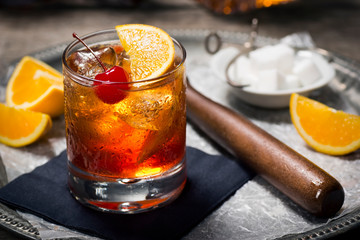 Old Fashioned Cocktail On Ice with Cherry and Orange Garnish, Sugar Cubes, and Muddler on Tray Wall mural