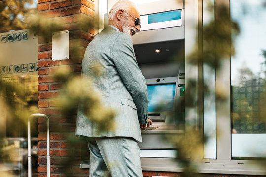 Senior man using bank credit card and typing pin code on keypad of ATM machine.