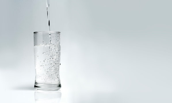 pour water into the glass on a white background