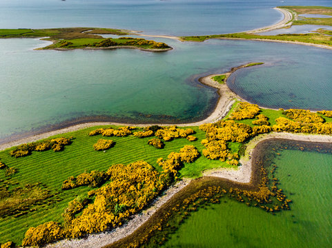 Aerial view of vivid emerald-green waters and islands near Westport town along the Wild Atlantic Way, County Mayo, Ireland.