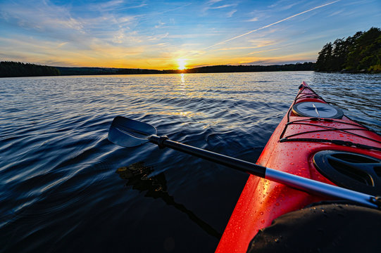 red plastic kayak on calm water in the sunset