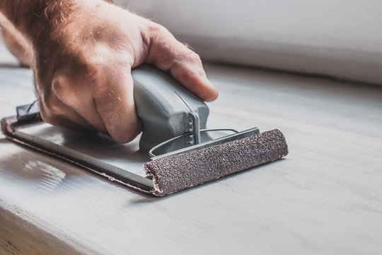 Close up of master's hand with grinding bar with coarse sandpaper