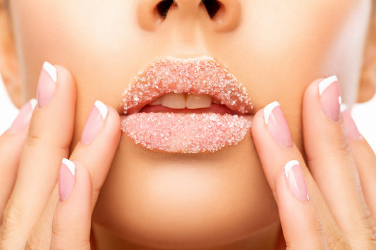 woman applying Sugar on her Lips. Close up  beautiful  photo Lip Scrub. beauty. Lips of Beautiful young Woman covered with Sugar, Closeup