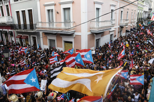 Demonstrators chant and wave Puerto Rican flags to celebrate the official resignation of now ex-governor of Puerto Rico Ricardo Rossello, in San Juan, Puerto Rico