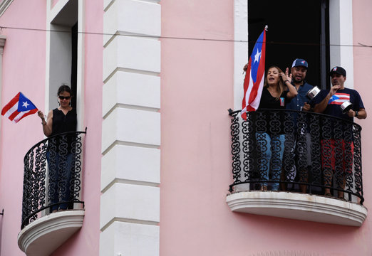 Demonstrators chant and wave Puerto Rican flags as they celebrate the official resignation of now ex-governor of Puerto Rico Ricardo Rossello, in San Juan, Puerto Rico