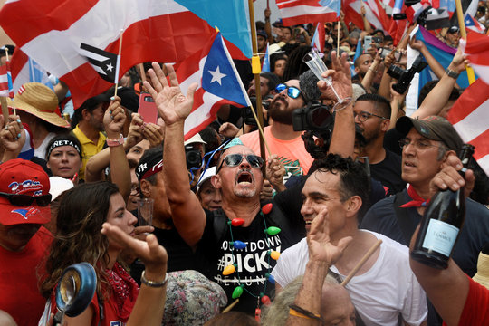 Demonstrators chant, wave Puerto Rican flags, and drink champagne celebrating the official resignation of now ex-governor of Puerto Rico Ricardo Rossello, in San Juan