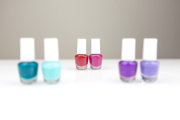Different nail polishes grouped by two by shade with two in the miidle in a focus and the rest are blurred. Red and pink