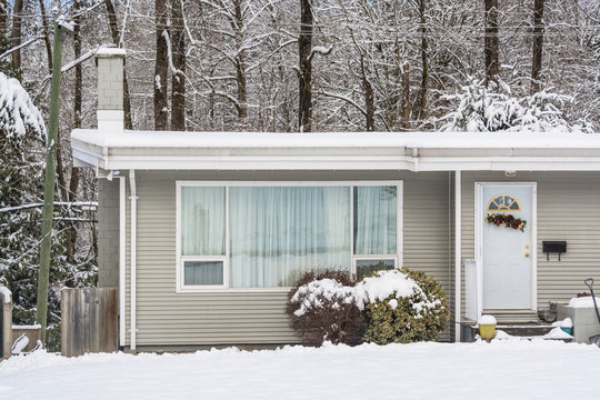 Entrance of residential house with front yard in snow on winter day