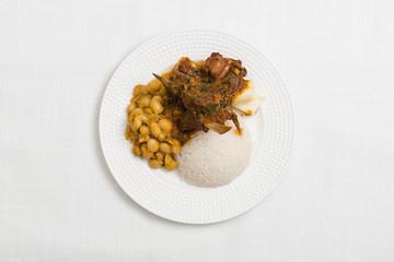 "Delicious dish of Peruvian food "" cabrito"" on white textured background"