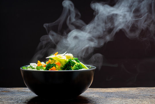 The steam from the vegetables carrot broccoli Cauliflower in a black bowl , a steaming. Boiled hot Healthy food on table on black background,hot food and healthy meal concept