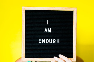 I Am Enough Written on a Letterboard on a Yellow Background