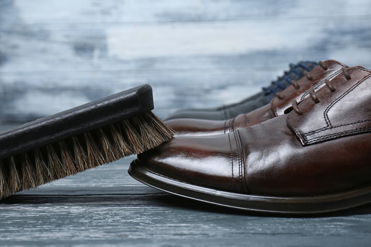 Men's leather shoes and cleaning brush on grey table