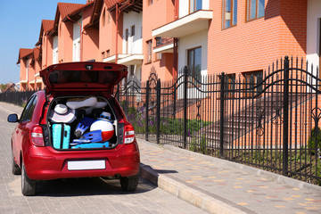 Family car with open trunk full of luggage in city. Space for text