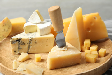 Different types of delicious cheese in wooden plate, closeup Fotobehang