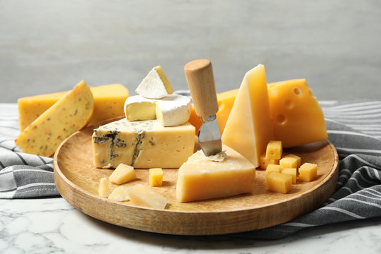 Wooden plate with different types of delicious cheese on marble table against light background