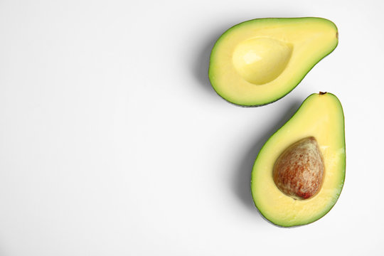 Cut fresh ripe avocado on white background, top view