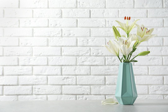 Vase of beautiful lilies on table against  white brick wall, space for text