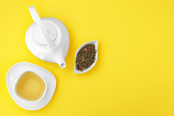 Composition with tea on yellow background, flat lay. Space for text