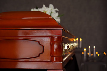 Wooden casket with white lilies in funeral home, closeup