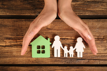 Woman holding hands near figures of house and family on wooden background, top view