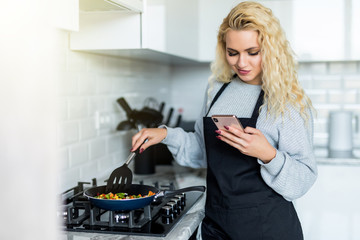 Beautiful young woman cooking healthy dinner using frying pan, using mobile phone in the kitchen