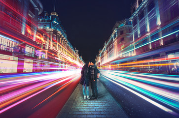 Foto auf Acrylglas London roten bus Kissing couple in the center of Regent Street, London at night