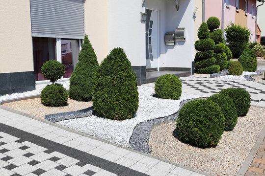 Modern front yard with decorative gravel and boxwoods