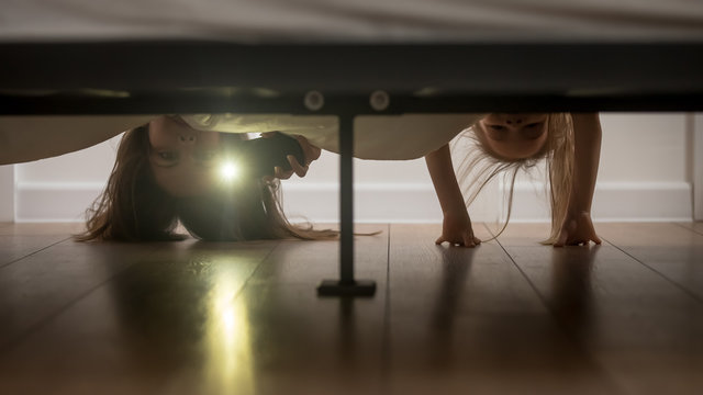 Mother and daughter shine a flashlight looking under the bed