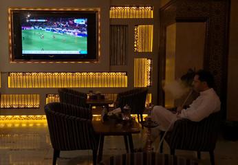 A Saudi man smokes shisha while watching a broadcast of Bundesliga highlights, pirated by beoutQ, at a local cafe in Khobar