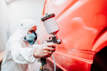 industry details - mechanic engineer using spray gun and painting a red car