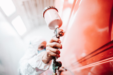 close up of male holding spray gun and painting a car