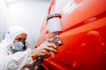mechanic worker painting a car in a special painting box, wearing a full body costume and protection gear Wall mural