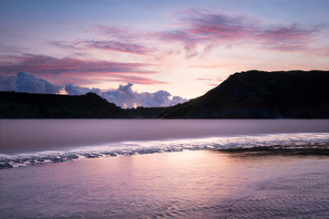 Photo sur Plexiglas Rose clair / pale Beautiful colorful Summer sunrise landscape image of Three Cliffs Bay in South Wales