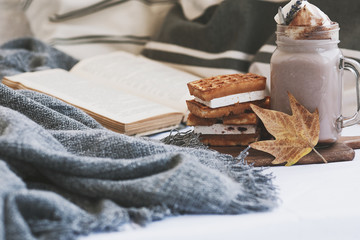 mug of hot cocoa with waffles on the bed. autumn mood