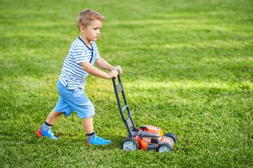 Happy 3 year old boy having fun mowing lawn