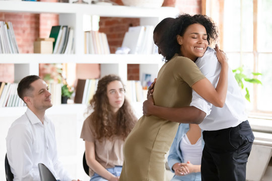 Woman psychologist addiction counsellor hugging supporting guy at group session