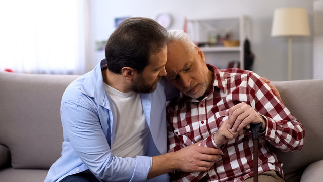 Middle-aged son comforting retiree terminally ill father, suffering pain, care